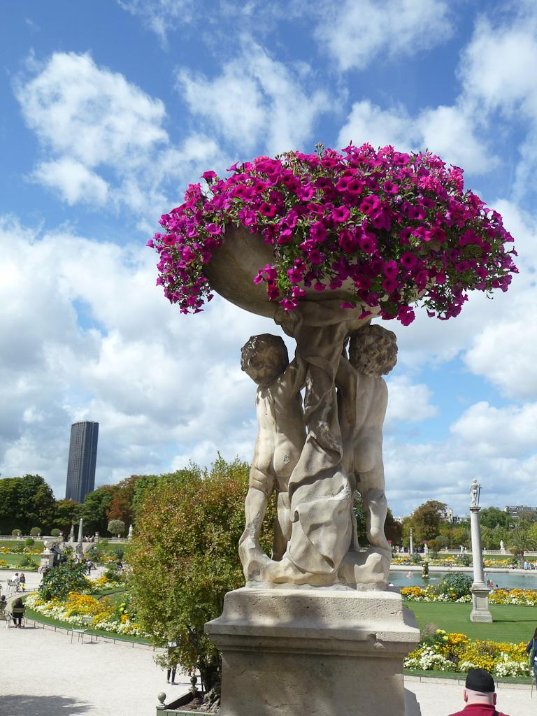 Vasque de surfinias soutenue par deux statues d'angelots, décorations florales estivales, jardin du Luxembourg, Paris 6e (75)