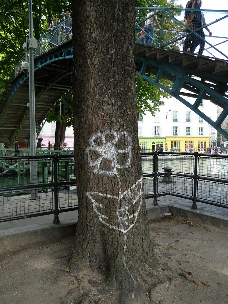 Fleur dessinée sur le tronc d'un arbre le long du Canal Saint-Martin, quai de Jemmapes, Paris 10e (75)