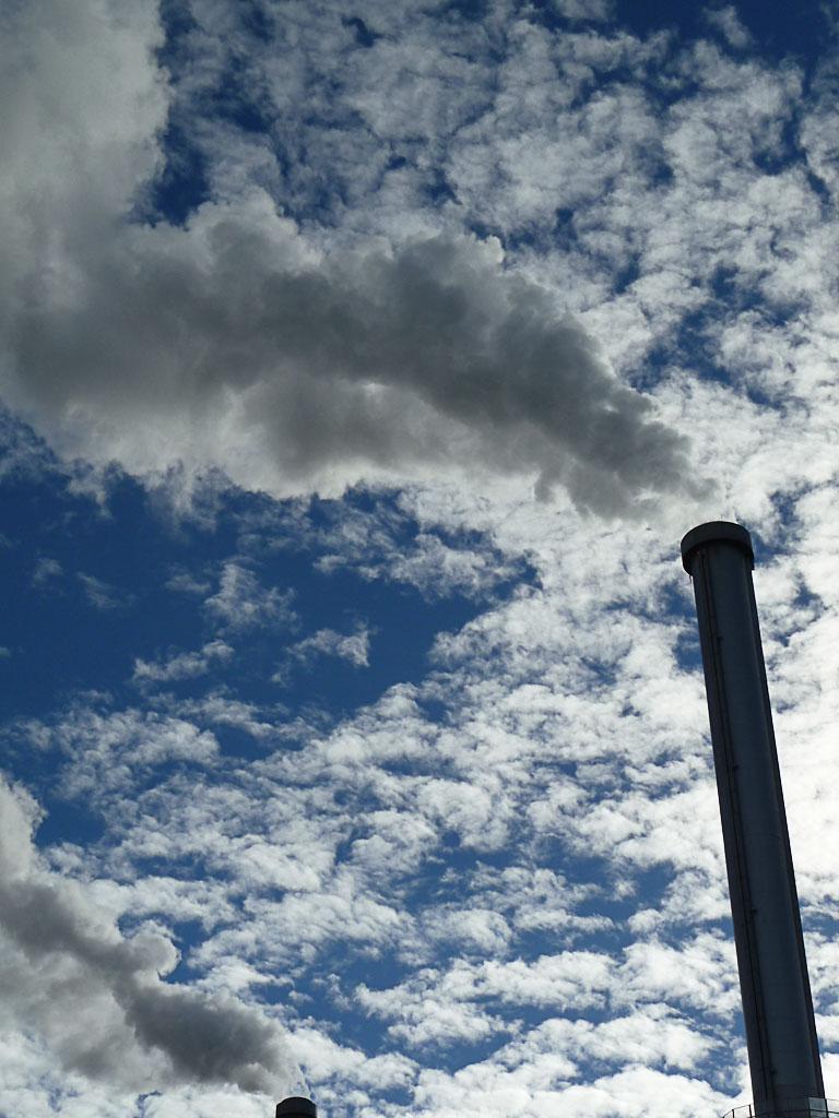 Fumées sortant des cheminées du centre multifilière Syctom sur fond de ciel bleu avec des nages blancs, Ivry-sur-Seine (94)