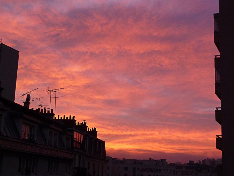 Ciel rougeoyant au lever du soleil au-dessus de la rue de Nantes, Paris 19e (75)